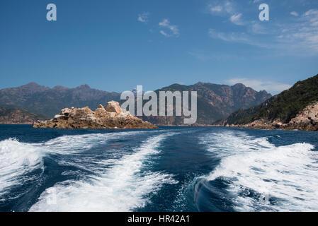 Powerful foam trace is receding along the steep coastal cliffs in the Gulf of Porto. - Stock Photo