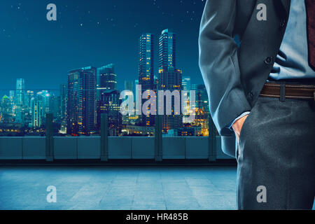 Body of business man with hand inside pocket over city background - Stock Photo