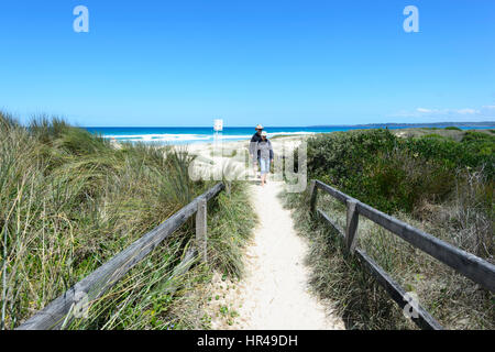 Two persons walking on the path to Conjola Beach, Shoalhaven, South Coast, New South Wales, NSW, Australia - Stock Photo