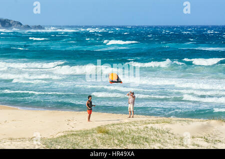 Two persons flying a kite on the beach, Potato Point, New South Wales, Australia - Stock Photo