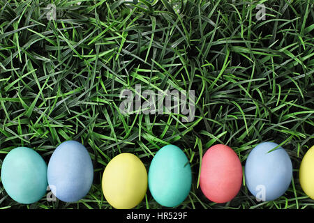 Overhead view of colorful Easter eggs lined up in a row over a background of grass. Flat lay style. - Stock Photo