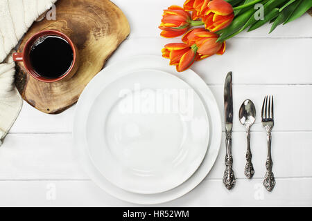 Overhead shot an empty dinner plate with coffee and a bouquet of springtime tulips over a white wood table top. - Stock Photo
