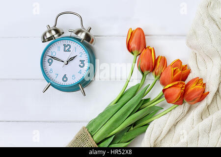 Alarm clock with a beautiful bouquet of tulips and a cozy blanket shot from above in a flatlay style over a wood - Stock Photo