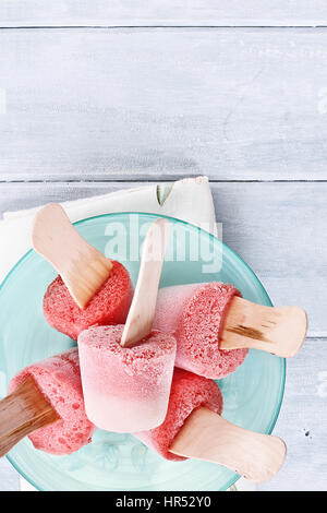Strawberry popsicles made from strawberries and yogurt over a wood table top. Shot from overhead. - Stock Photo