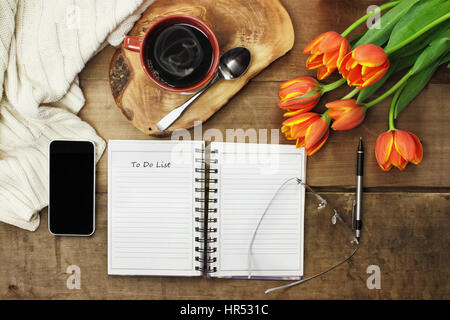 Overhead of an open book, cell phone, coffee and flowers over a wood table top ready to plan an agenda. Flat lay - Stock Photo