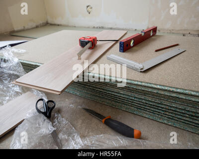 Repairing apartment's  floor . Plates of pressed wood chips. Laminate. Measuring the Tools, building level, tape - Stock Photo