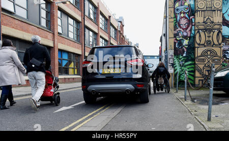Wheelchair user struggles to pass by badly parked car on pavement and double yellow lines in Brighton UK - Stock Photo