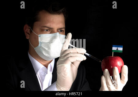 Young businessman injecting chemicals into an apple with Lesotho flag on black background - Stock Photo