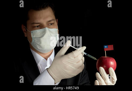 Young businessman injecting chemicals into an apple with Myanmar flag on black background - Stock Photo