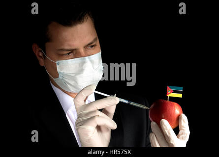 Young businessman injecting chemicals into an apple with Mozambique flag on black background - Stock Photo