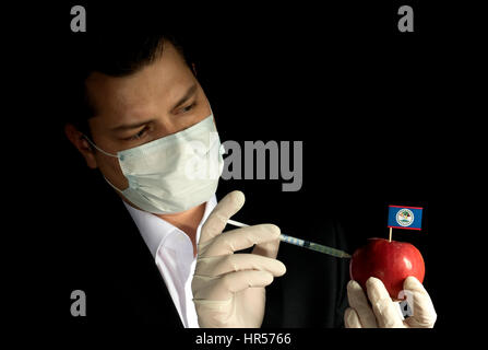 Young businessman injecting chemicals into an apple with Belize flag on black background - Stock Photo