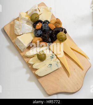 platter of cheese on a wooden board - Stock Photo