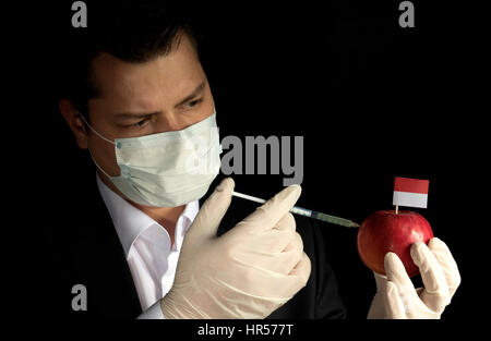 Young businessman injecting chemicals into an apple with Monaco flag on black background - Stock Photo
