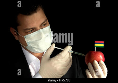 Young businessman injecting chemicals into an apple with Mauritius flag on black background - Stock Photo