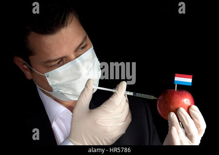 Young businessman injecting chemicals into an apple with Luxembourg flag on black background - Stock Photo