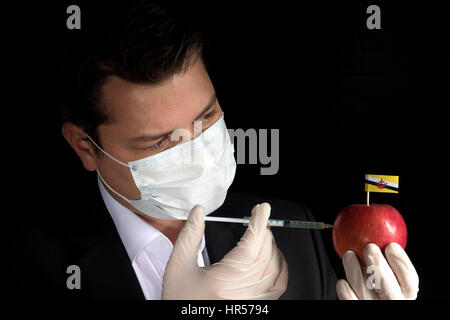 Young businessman injecting chemicals into an apple with Brunei flag on black background - Stock Photo