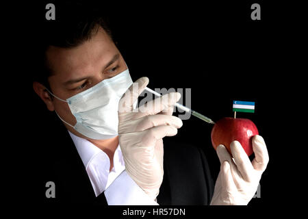 Young businessman injecting chemicals into an apple with Uzbekistan flag on black background - Stock Photo