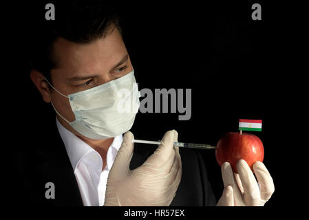 Young businessman injecting chemicals into an apple with Tajikistan flag on black background - Stock Photo