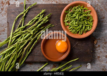 high-angle shot of some wild asparagus and some earthenware bowls with chopped  asparagus and a cracked egg, the - Stock Photo
