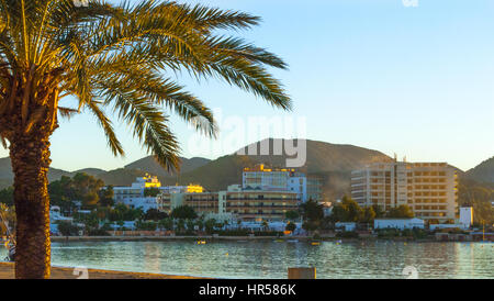 Late afternoon sun falls on the bay.  St Antoni de Portmany, Ibiza, Spain.  Hotels along the shoreline in golden - Stock Photo