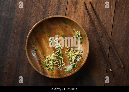 Top view leftover food Japanese ramen dried noodles with chopsticks on rustic wooden table. - Stock Photo