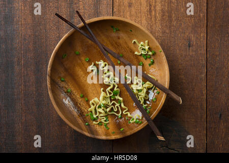 Top view leftover food dried noodles with chopsticks on rustic wooden table. - Stock Photo