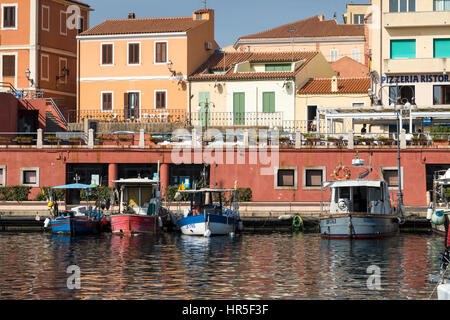 Moored Fishing Boats and Waterfront Buildings in the Port of La Maddalena, Sardinia, Italy. - Stock Photo