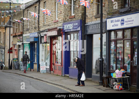 Bunting and flags flying on Hare Hill Road, ,Littleborough Village stone terraced shops, Rochdale, Lancashire, England, - Stock Photo