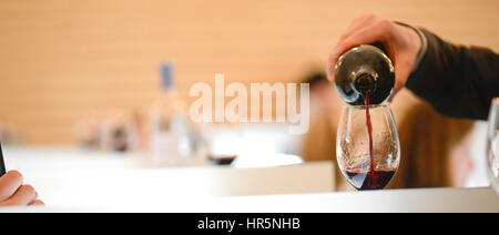 Tasting wine in a vinery-A man's hand is pouring red wine into a glass with a corkscrew set down. Lot of wine bottles - Stock Photo