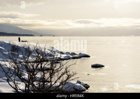 tourists enjoying the rising sun over snowy mountain and calm fjord in winter - Stock Photo