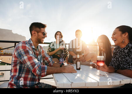 Multiracial group of friends having cocktail party on the rooftop. Young men and women sitting around table with - Stock Photo