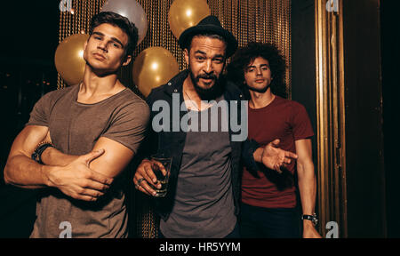 Portrait of three young men standing in a nightclub. Stylish group of men at pub.
