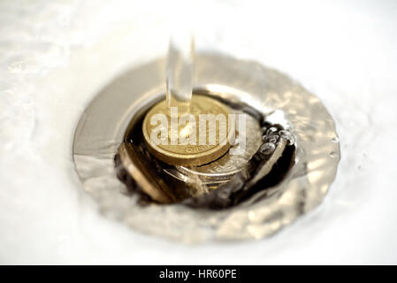 British money including a one pound coin stuck in a sink drain plughole as water flows over the coins. - Stock Photo