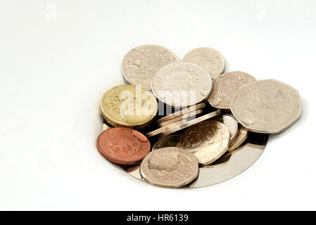 Pile of English currency coins stuck in the sink of a bath or kitchen drain. Copyspace area for savings investments - Stock Photo