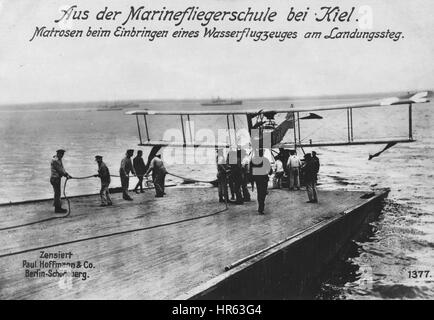 German World War I photographic postcard depicting sailors with a seaplane at the landing stage at a naval flying - Stock Photo
