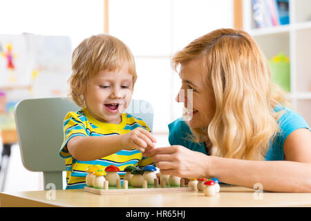 Woman with child talking and smiling while playing educational toys together in daycare centre - Stock Photo