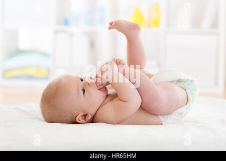 Funny little baby wearing a nappy playing with his legs in nursery. Cute kid sucking his feet. Child after bath - Stock Photo