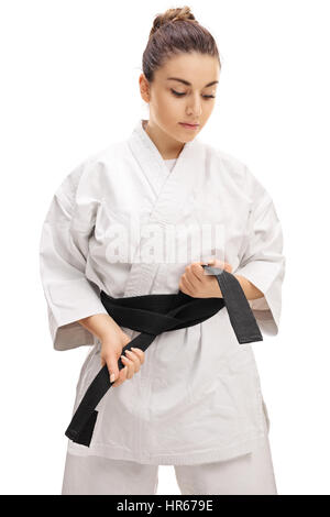 Karate girl tying a black belt isolated on white background - Stock Photo