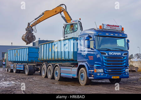 A crane with hydraulic elevated cab and equipped with a sorting grapple is loading a container on lorry trailer - Stock Photo