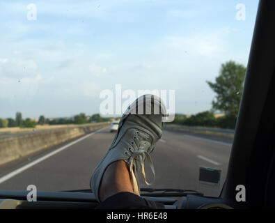 Vans Canvas shoe on the dashboard of a car speeding on a highway - Stock Photo
