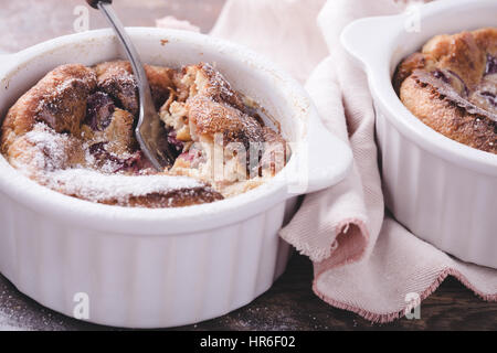 Homemade traditional  french dessert cherry clafoutis in ceramic ramekins on rustic table - Stock Photo