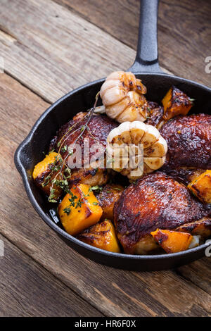 Homemade  roasted  chicken thighs with with butternut, thyme and garlic in cast iron pan on rustic wooden table - Stock Photo