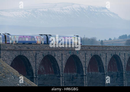 An Arriva Rail Northern passenger diesel train going across the Ribblehead Viaduct on a grey winter day with snow - Stock Photo