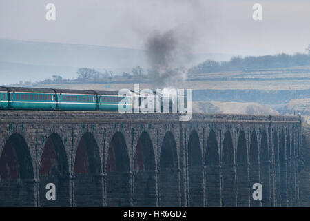 Locomotive, No. 60163 Tornado, a brand new Peppercorn A1 Pacific, travels across the Ribblehead Viaduct on a grey - Stock Photo
