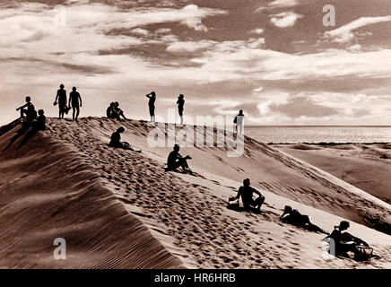 Timeless, temperate, toned B&W image of a surreal arrangement of people on the crest of a sand dune, in Maspalomas - Stock Photo