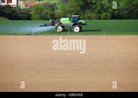 Green tractor on field. Tractor fertilizes green wheat field. Tractor spraing water on crops. Free space for text - Stock Photo