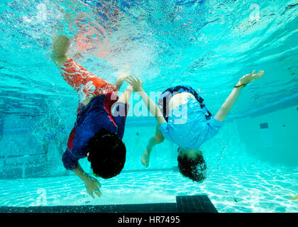 kids swimming underwater in pool enjoying the relaxation of summer stock photo - Kids Swimming Underwater