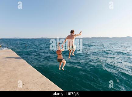 Young couple jump into the sea in Zadar Croatia - Stock Photo