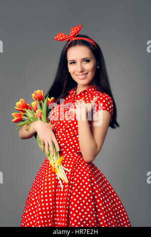 Cute Girl in Retro Red Polka Dress with Tulips - Stock Photo
