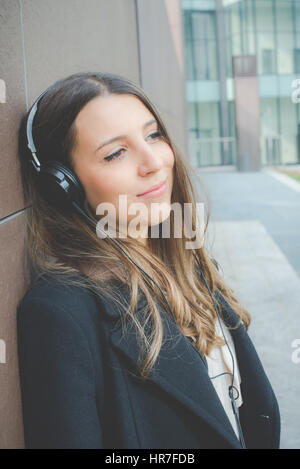 young authentic business woman relaxes listening to music in the city - Stock Photo